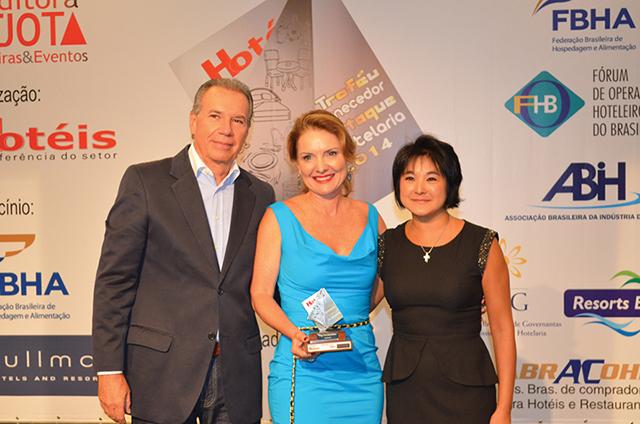 À esquerda da foto, o Diretor da VAG Confecções, Fernando Gomes, ladeado pela também diretora da empresa, Vanessa Andrade, recebendo o troféu de Regina Segui, Diretora de Produto e Suprimentos da Atlantica Hotels