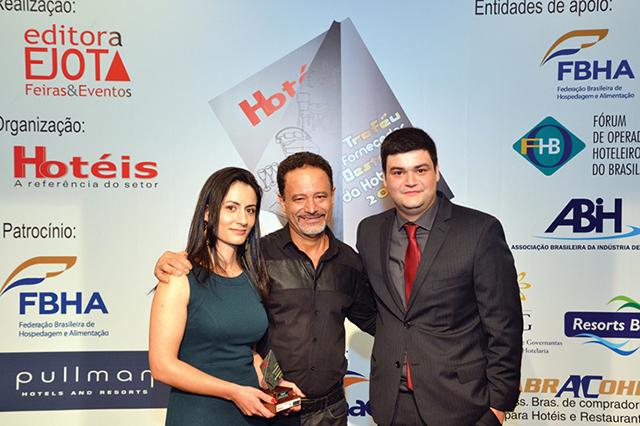 No centro da foto, o Chef executivo da rede de hotéis Estamplaza, Waldomiro Santos, entregando o Trofeu a Matheus Quincozes (Diretor Executivo) e Ana Elena Carboni (Diretora de Projetos) da empresa Vega IT